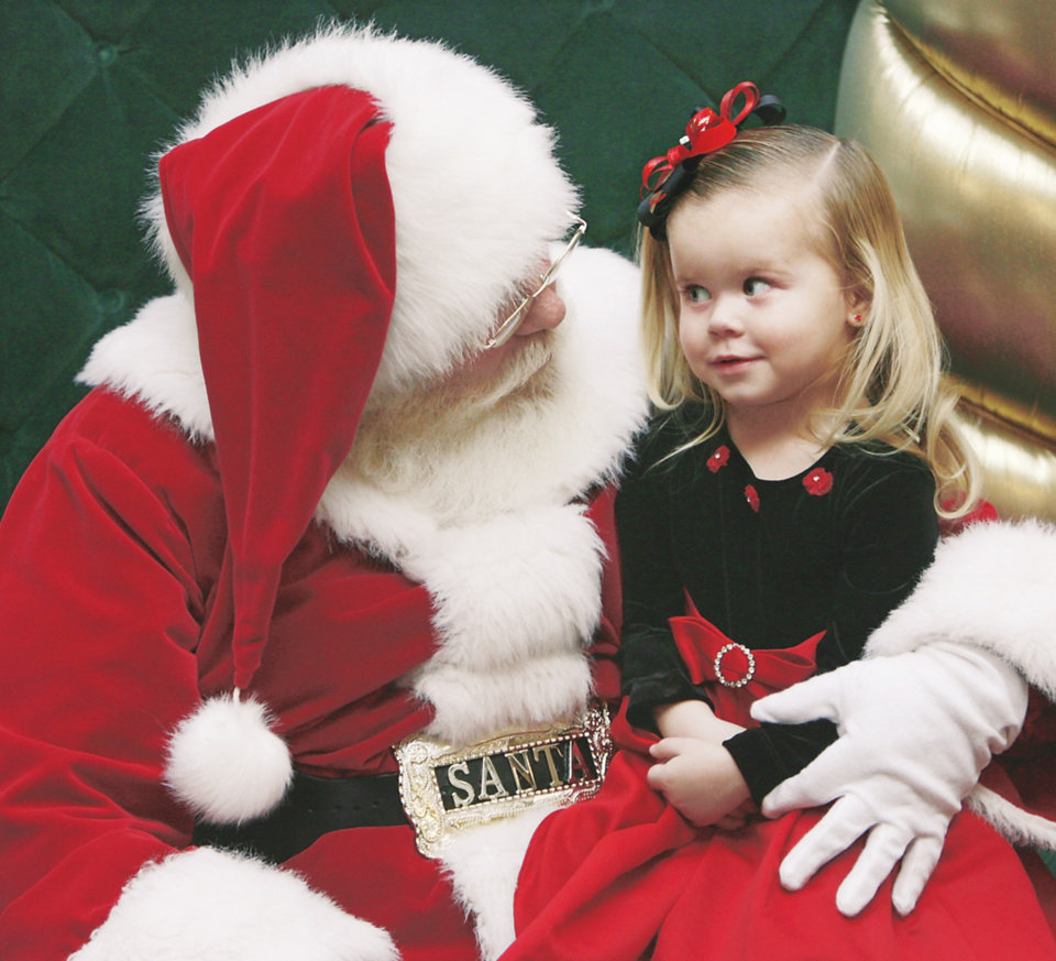 Santa Claus tries to make 2-year-old Sienna Smithson of Yukon smile while having their picture made at Penn Square Mall on Dec. 12. PHOTOS BY JIM BECKEL, THE OKAHOMAN
