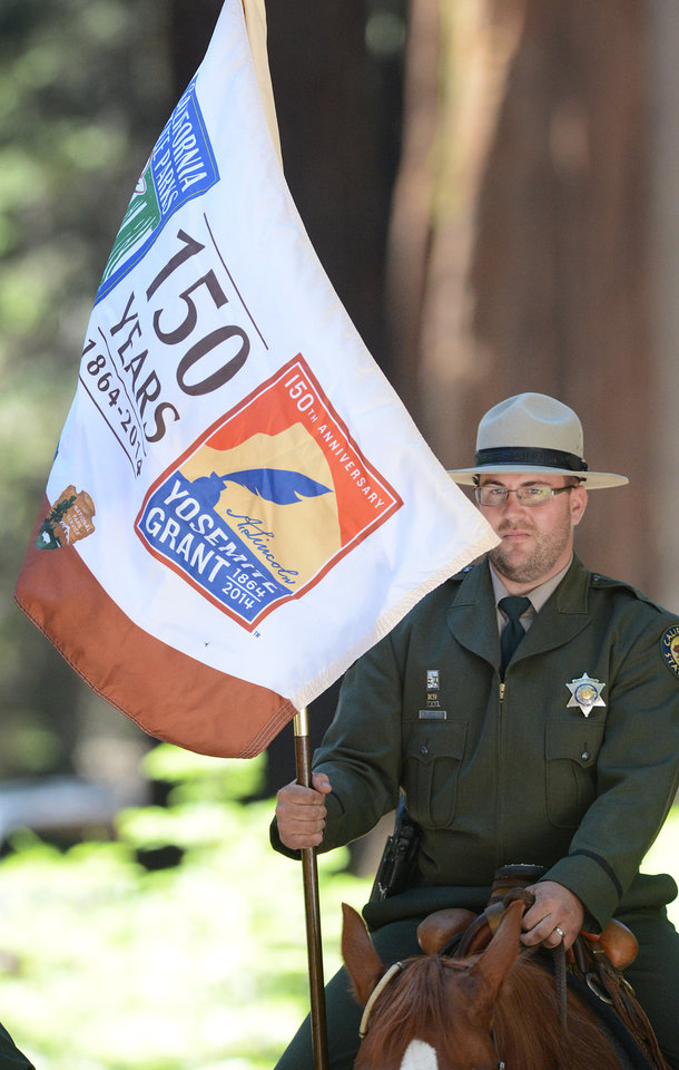 Photo - A park ranger holds a flag commemorating the 150th anniversary of the Yosemite Land Grant during the Yosemite Grant sesquicentennial ceremony at Yosemite National Park's Mariposa Grove Monday, June 30, 2014. On June 30, 1864, President Abraham Lincoln signed the Yosemite Land Grant which eventually led to the national parks system. (AP Photo/The Fresno Bee, Craig Kohlruss)