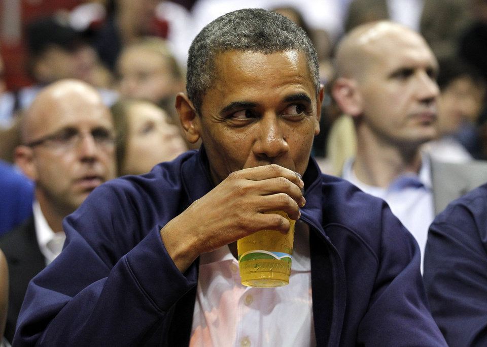 Photo - FILE - In this July 16, 2012 file photo, President Barack Obama sips his beer as he watches Team USA and Brazil during the first half of an Olympic men's exhibition basketball game, in Washington. Obama and his team frequently talk about the president's fondness for beer, and Obama has been photographed many times downing a beer, including an appearance at the Iowa State Fair last month. Being identified as a beer drinker is an easy way for Obama to connect with votes and serves as a not-so-subtle reminder that his Republican rival Mitt Romney, a Mormon, doesn't drink. (AP Photo/Alex Brandon, File) ORG XMIT: WX202