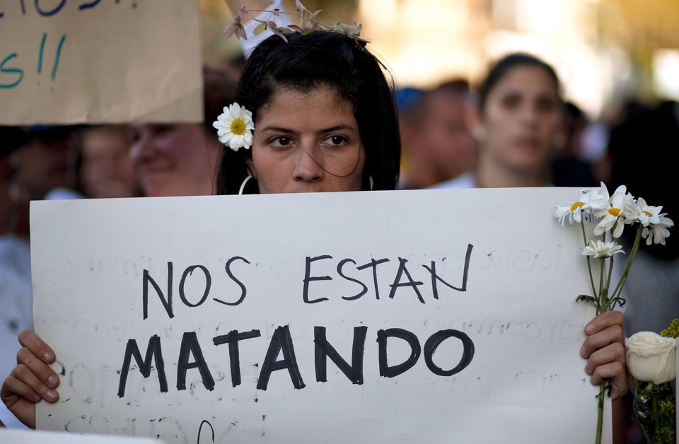 Photo - An opposition demonstrator holds a poster that reads in Spanish