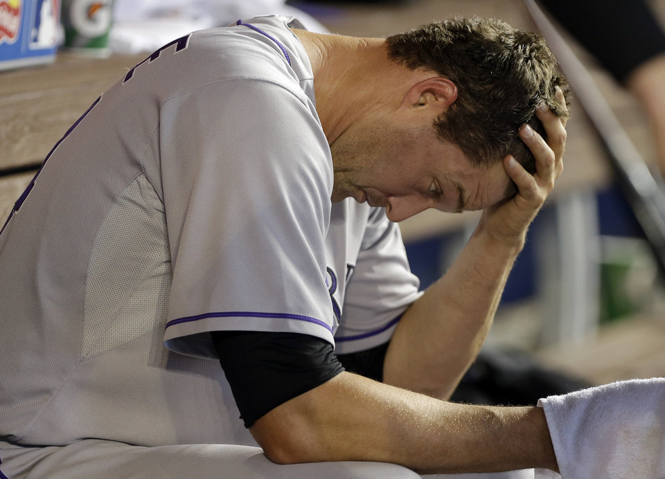 Photo - Colorado Rockies relief pitcher Matt Belisle sits in the dugout after pitching in the eighth inning when the Miami Marlins scored four runs during a baseball game, Thursday, April 3, 2014, in Miami. The Marlins defeated the Rockies 8-5. (AP Photo/Lynne Sladky)