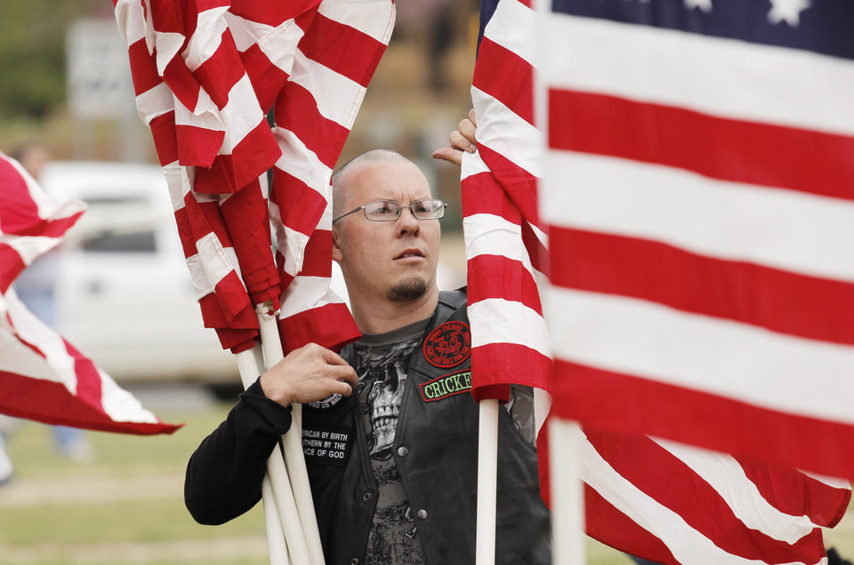 """Marcus """"Cricket"""" Troutman helps to plant American flags in honor of children who died in America in 2011 in the fields south of the state Capitol Sunday, April 7, 2013. Photo by Doug Hoke, The Oklahoman"""