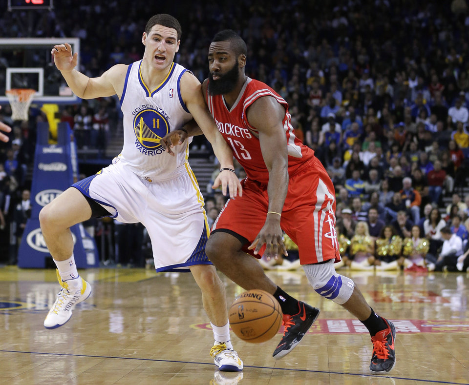 Houston Rockets' James Harden (13) dribbles next to Golden State Warriors' Klay Thompson (11) during the first half of an NBA basketball game in Oakland, Calif., Tuesday, Feb. 12, 2013. (AP Photo/Marcio Jose Sanchez)