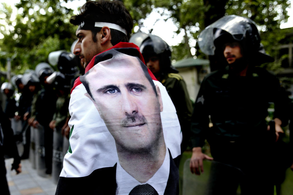 Photo - An Syrian man wrapped in a Syrian flag with a portrait of President Bashar Assad, walks past anti riot police during an anti-Israeli demonstration in front of the UN office in Tehran, Iran, Monday, May 6, 2013. Iran Condemns Israeli Air strikes on Syria and urged countries in the region to stand against the attack. (AP Photo/Ebrahim Noroozi)