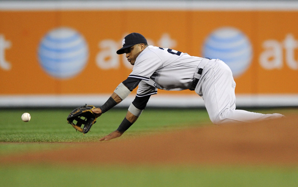 Photo -   New York Yankees second baseman Robinson Cano dives for a grounder by Baltimore Orioles' Nick Markakis during the first inning of a baseball game, Thursday, Sept. 6, 2012, in Baltimore. Markakis was out at first on the play. (AP Photo/Nick Wass)