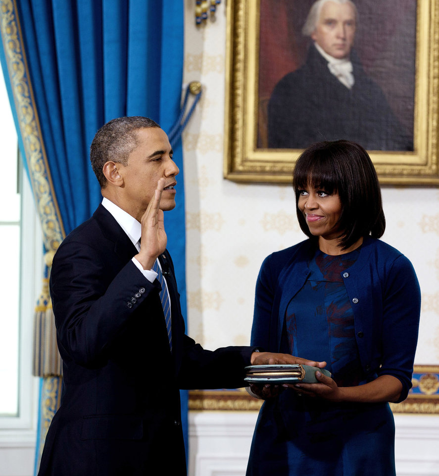 President Barack Obama is officially sworn-in by Chief Justice John Roberts, not pictured, in the Blue Room of the White House Sunday, Jan. 20, 2013, in Washington, as first lady Michelle Obama holds the Robinson Family Bible. (AP Photo/Doug Mills, The New York Times, Pool) ORG XMIT: NYNYT103