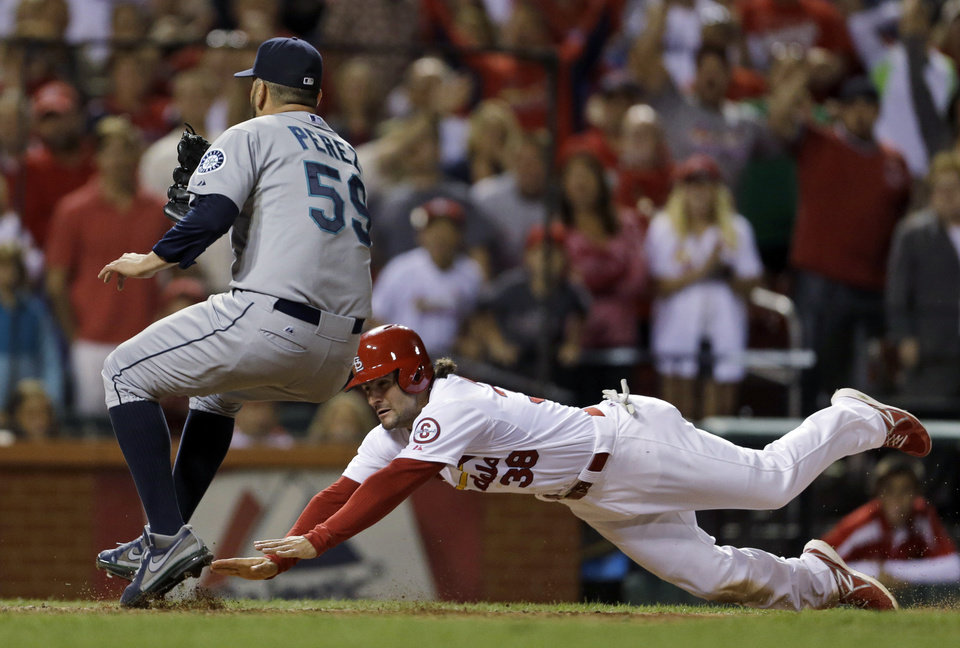 Photo - St. Louis Cardinals' Pete Kozma, right, scores the game-winning run on a passed ball as Seattle Mariners relief pitcher Oliver Perez covers home during the 10th inning of a baseball game Friday, Sept. 13, 2013, in St. Louis. The Cardinals won 2-1. (AP Photo/Jeff Roberson)