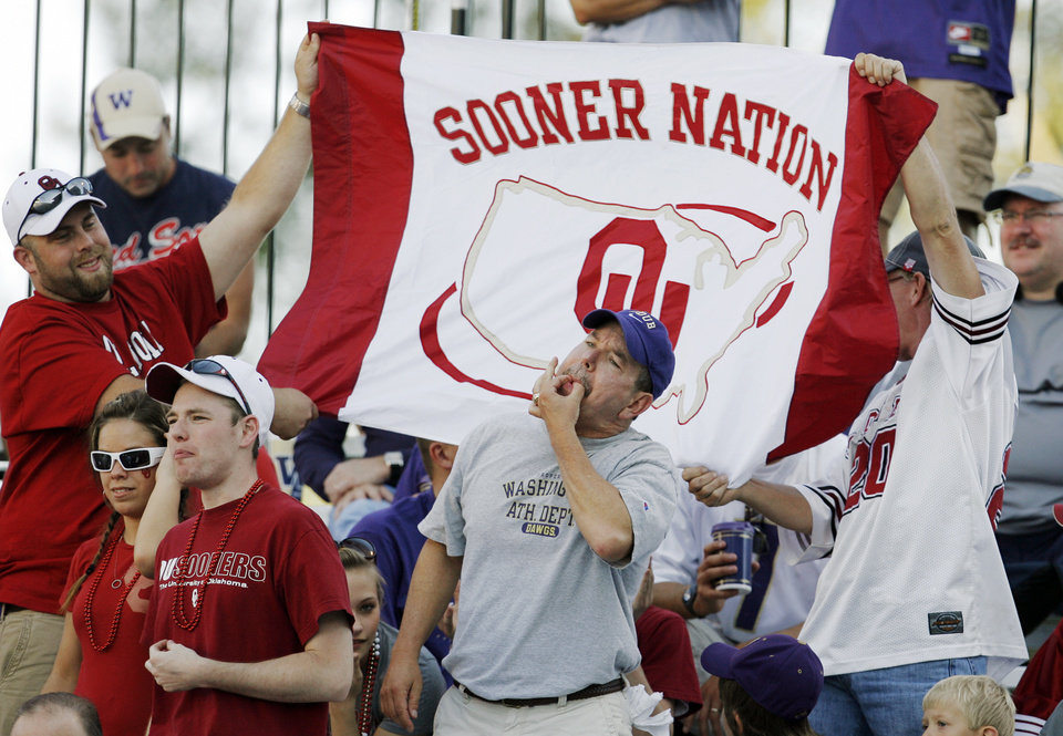 Photo - A Washington fan whistles for his team as Oklahoma fans hold a Sooner Nation flag before the college football game between Oklahoma and Washington at Husky Stadium in Seattle, Wash., Saturday, September 13, 2008. BY NATE BILLINGS, THE OKLAHOMAN
