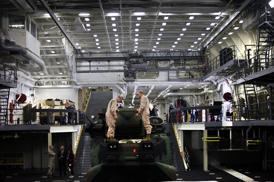 Photo - Tanks and assault vehicles are displayed during the media tour of the USS Arlington in Norfolk, Va., on Friday, April 5, 2013. The Navy commissioned the USS Arlington in front of about 5,000 people in its new home port of Naval Station Norfolk. The amphibious transport dock is one of three ships named after 9/11 crash sites, and 200 pounds of steel salvaged from the Pentagon's wreckage have been forged into a pentagon to be put on a permanent display aboard the ship in a memorial room. The ship also has 184 gold stars throughout the ship in honor of those who died when American Airlines Flight 77 crashed into the Pentagon on Sept. 11, 2011. (AP Photo/The Virginian-Pilot, The' N. Pham)  MAGS OUT