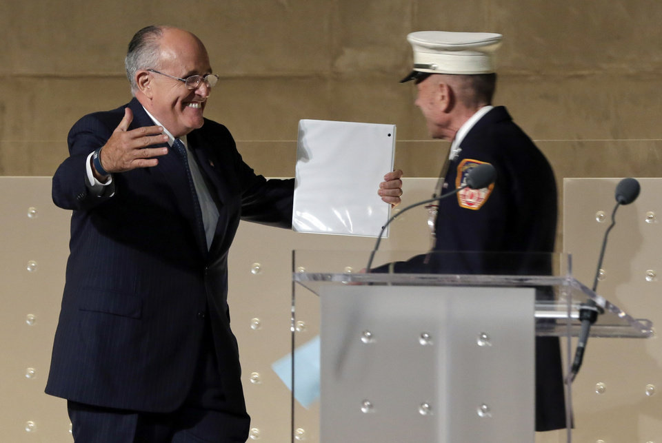 Photo - Former New York Mayor Rudolph Giuliani, left, greets New York City firefighter Mickey Kross before his speech during the dedication ceremony in Foundation Hall, of the National September 11 Memorial Museum, in New York, Thursday, May 15, 2014. (AP Photo/Richard Drew, Pool)