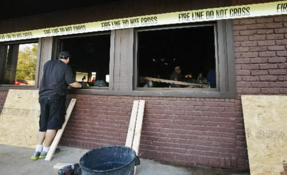 Photo - A worker prepares to board up broken out front windows to Hideaway Pizza, 6616 N Western Ave., as damage is being inspected after an early morning fire at the popular pizza establishment in Oklahoma City Tuesday, Sept. 25, 2012. Photo by Paul B. Southerland