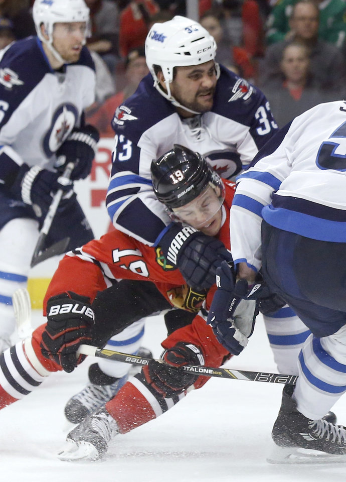 Photo - Winnipeg Jets defenseman Dustin Byfuglien (33) takes Chicago Blackhawks center Jonathan Toews (19) down after Toews' shot on goal during the second period of an NHL hockey game Sunday, Jan. 26, 2014, in Chicago. (AP Photo/Charles Rex Arbogast)