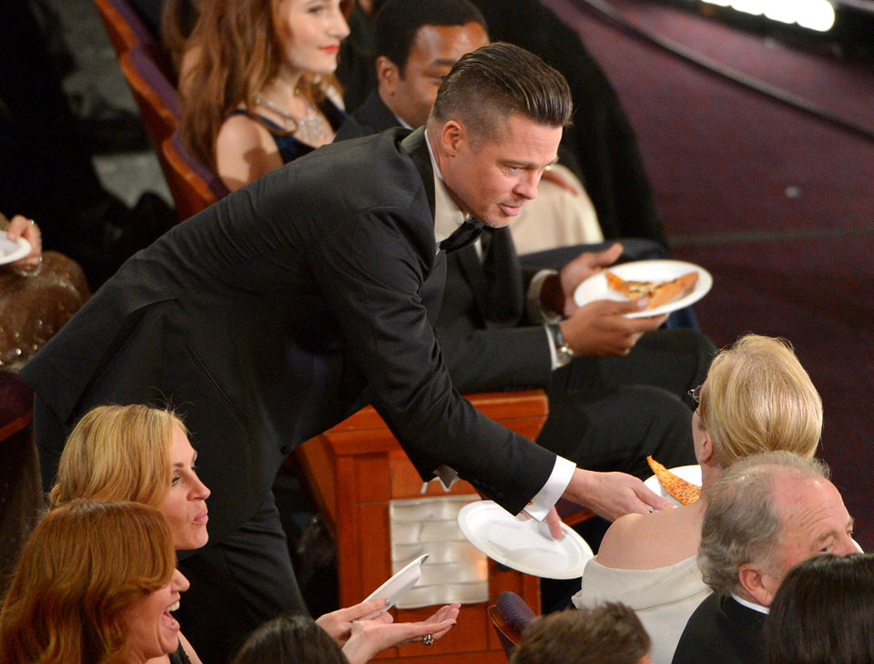 Photo - Brad Pitt, left, shares pizza with Meryl Streep in the audience during the Oscars at the Dolby Theatre on Sunday, March 2, 2014, in Los Angeles.  (Photo by John Shearer/Invision/AP)