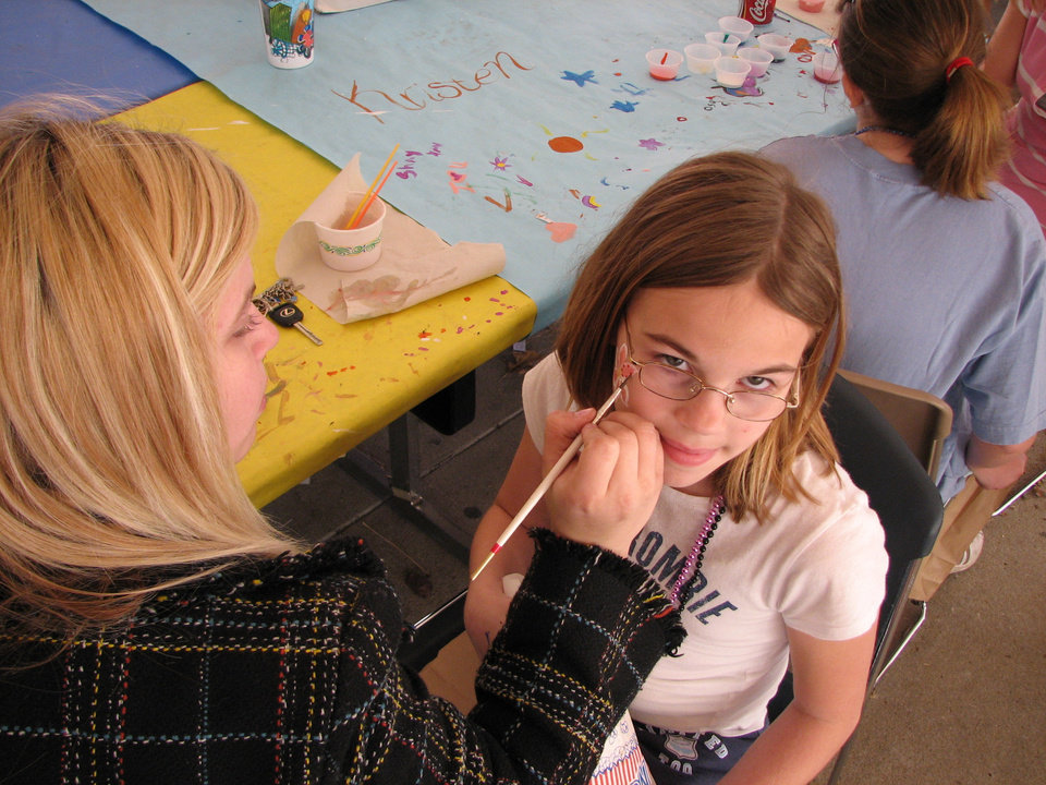 Rylie Myers, 10, has a flower painted on her face by Canadian Valley Technology Center student Ashleigh Stone, a 16-year-old Commerical Graphic Arts student from Piedmont High School. Community Photo By: Bill Kramer, Canadian Valley Tech. Ctr. Submitted By: Bill, Yukon