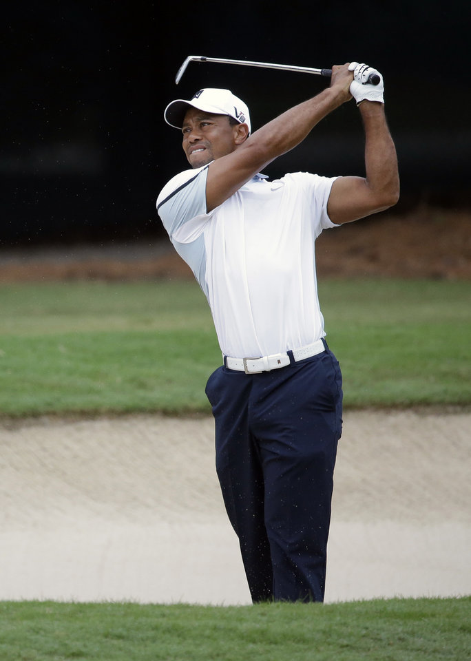 Photo - Tiger Woods hits out of the bunker on the fourth hole during the third round of play in the Tour Championship golf tournament at East Lake Golf Club, in Atlanta, Saturday, Sept. 21, 2013. (AP Photo/David Goldman)