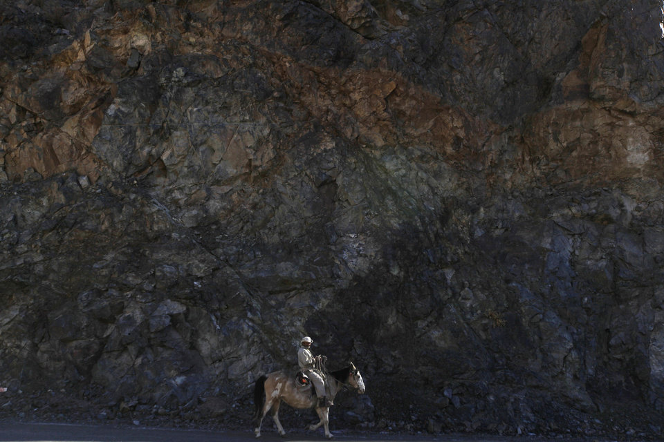 Photo - In this May 23, 2013 photo, Juan Guerrero rides past a wall of rock as he rides into El Corral, a small town of about 200 inhabitants, mostly from the Diaguita ethnic group, near the facilities of Barrick Gold Corp's Pascua-Lama project in northern Chile. The Diaguitas live in the foothills of the Andes, where for as long as anyone can remember they've drunk straight from the glacier-fed river that irrigates their orchards and vineyards with clean water. But since Barrick gold mine project moved in, the residents claim the river levels have dropped and some complain of cancerous growths and aching stomachs. (AP Photo/Jorge Saenz)