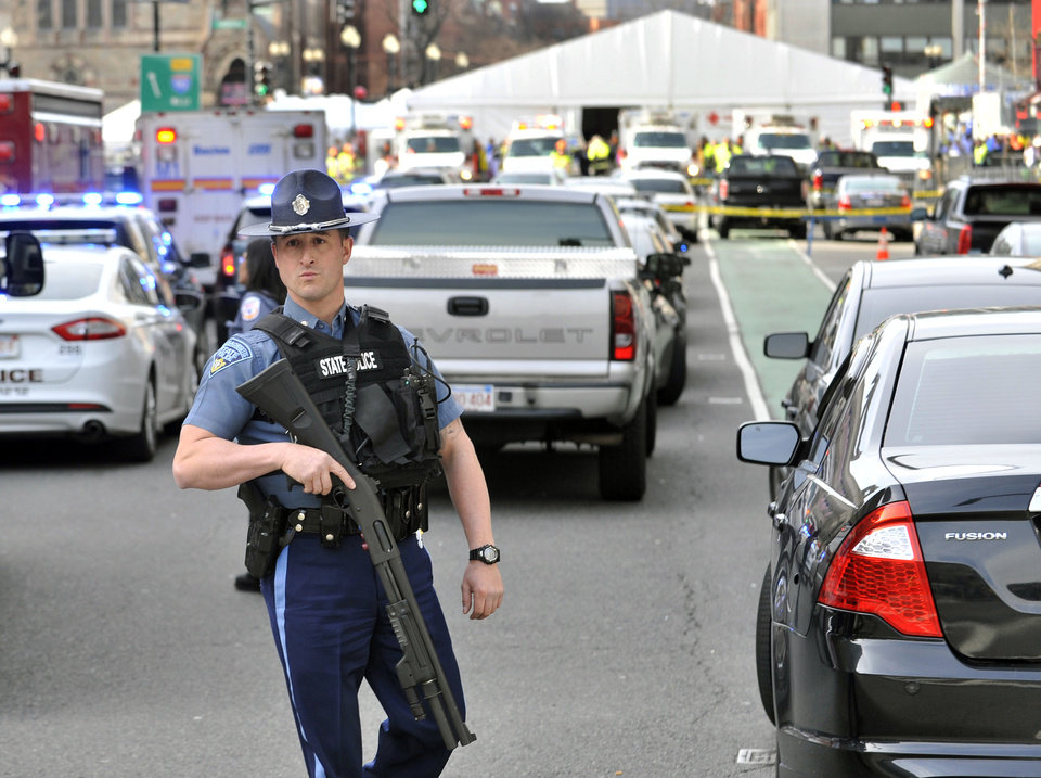 Photo - A Massachusetts state police officer guards the area containing the medical tent, rear, following an explosion at the 2013 Boston Marathon in Boston, Monday, April 15, 2013. Two explosions shattered the euphoria of the Boston Marathon finish line on Monday, sending authorities out on the course to carry off the injured while the stragglers were rerouted away from the smoking site of the blasts. (AP Photo/Josh Reynolds) ORG XMIT: BX103