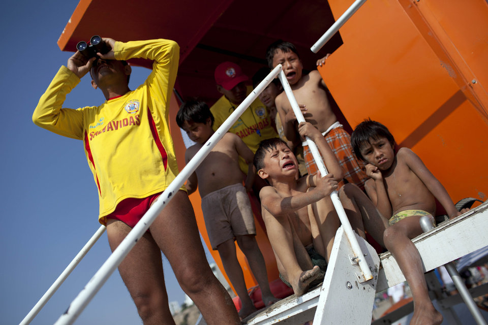 In this Jan. 27, 2013 photo, a lifeguard monitors swimmers as lost children wait to be reunited with their families at Agua Dulce beach in Lima, Peru. While Lima's elite spends its summer weekends in gate beach enclaves south of the Peruvian capital, the working class jams by the thousands on a single municipal beach of grayish-brown sands and gentle waves. On some weekends during the Southern Hemisphere summer, which runs from December until March, as many as 40,000 people a day visit the half-mile-long (kilometer-long) strip of Agua Dulce.  (AP Photo/Rodrigo Abd)