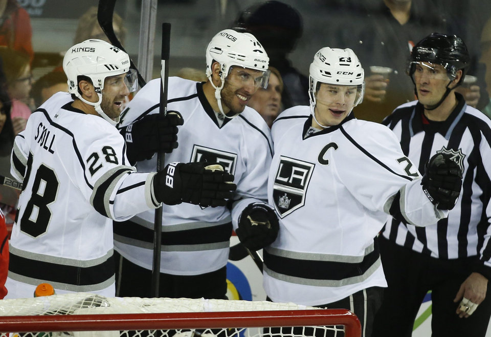 Photo - Los Angeles Kings' Dwight King, centre, celebrates his goal with teammates Jarret Stoll, left, and Dustin Brown, right, during third period NHL hockey action against the Calgary Flames in Calgary, Alberta, on Thursday Feb. 27, 2014. (AP Photo/The Canadian Press, Jeff McIntosh)