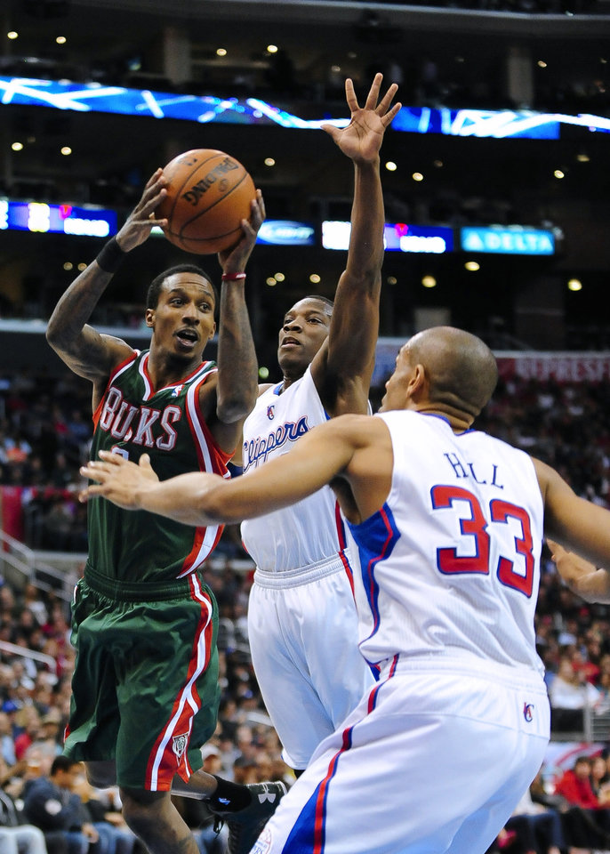 Photo - Milwaukee Bucks guard Brandon Jennings, left, looks for an opening against Los Angeles Clippers guard Eric Bledsoe, center, and forward Grant Hill (33) in the first half of an NBA basketball game, Wednesday, March 6, 2013, in Los Angeles.(AP Photo/Gus Ruelas)
