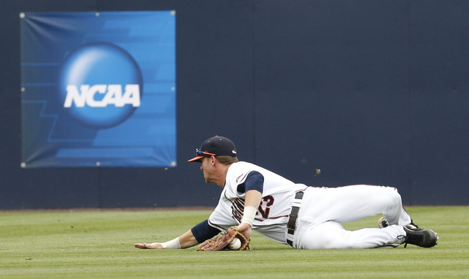 Photo - Virginia outfielder Derek Fisher (23) holds onto a fly ball during an NCAA College regional tournament baseball game against Bucknell in Charlottesville, Va., Friday, May 30, 2014. The play was ruled an out. (AP Photo/Steve Helber)