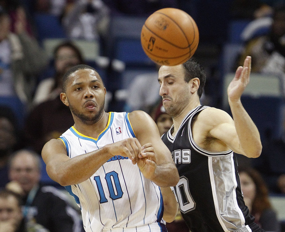 Photo - New Orleans Hornets guard Eric Gordon (10) passes the ball as San Antonio Spurs guard Manu Ginobili (20) plays defense in the second half of an NBA basketball game  in New Orleans, Monday, Jan. 7, 2013. (AP Photo/Bill Haber)