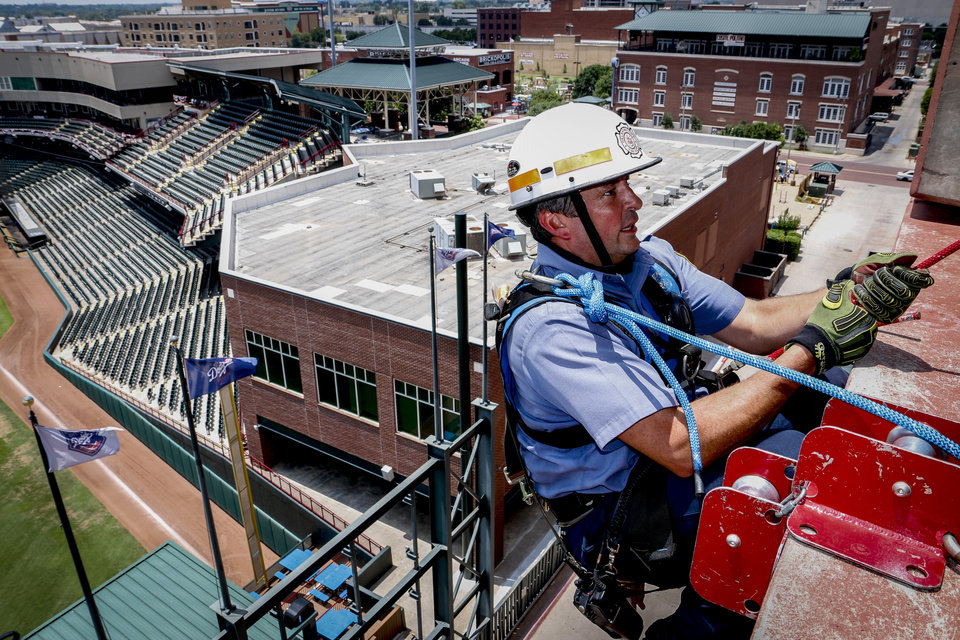 Photo -  Oklahoma City fire Capt. Brad Tobin prepares to repel down a parking garage on July 4. [Photo by Cort Smith, for The Oklahoman]
