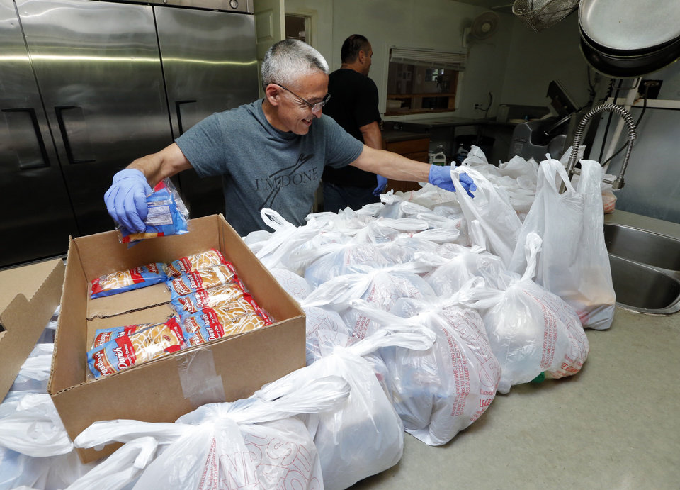 Photo -  Cook Nick Hendrick makes sack lunches for clients to take with them to work at the Christian Alcoholics & Addicts in Recovery (CAAIR) rehab center in Jay. [Photo by Steve Sisney, The Oklahoman]