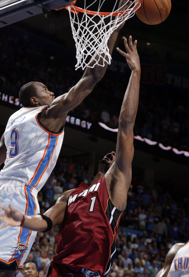 Photo - Oklahoma City's Serge Ibaka (9) blocks the shot of  Miami's Chris Bosh (1) during the NBA basketball game between the Miami Heat and the Oklahoma City Thunder at Chesapeake Energy Arena in Oklahoma City, Sunday, March 25, 2012. Photo by Sarah Phipps The Oklahoman