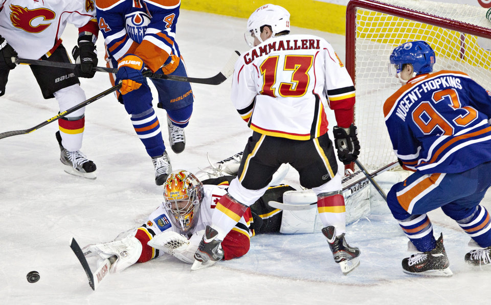 Photo - Calgary Flames goalie Joey MacDonald (35) makes the save as Mike Cammalleri (13) and Edmonton Oilers Ryan Nugent-Hopkins (93) look for the rebound during second period NHL hockey action in Edmonton, Alberta, on Monday April 1, 2013. (AP Photo/The Canadian Press, Jason Franson).