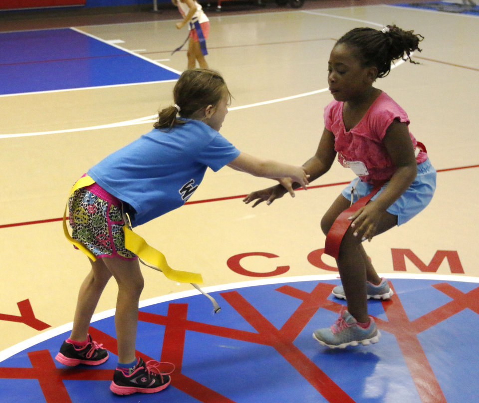 Photo -  Keelie Cullum, left, and Kalencia Roberts try to capture each other's flag Monday during the OCCC Summer Sports Camp on the Oklahoma City Community College campus.Photo by Paul Hellstern, The Oklahoman   PAUL HELLSTERN -  Oklahoman