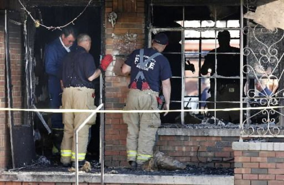 Photo - Okla. City Police Sgt. Mike Veasey, far left, firemen and arson investigators searching through the aftermath of a fatality house fire at 2535 SW 51 Street in Oklahoma City Monday, April 29, 2013. A 7-year-old boy died in the house fire late Sunday. Photo by Paul B. Southerland, The Oklahoman