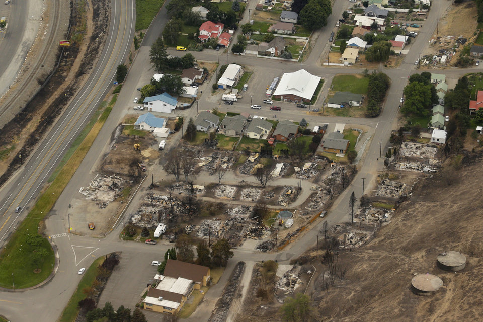 Photo - This aerial photo shows homes destroyed by wildfires in Pateros, Wash. on Thursday, July 24, 2014. Fire spokesman Pete Buist says the biggest wildfire in the state's history remains at 52 percent contained on Thursday. However, the weather forecast calls for hot and dry conditions to return over the next few days. (AP Photo)