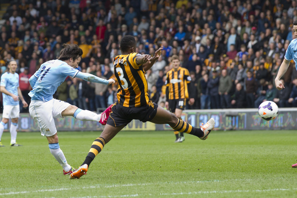 Photo - Manchester City's David Silva, left, scores against Hull City during their English Premier League soccer match at the KC Stadium, Hull, England, Saturday March 15, 2014. (AP Photo/Jon Super)