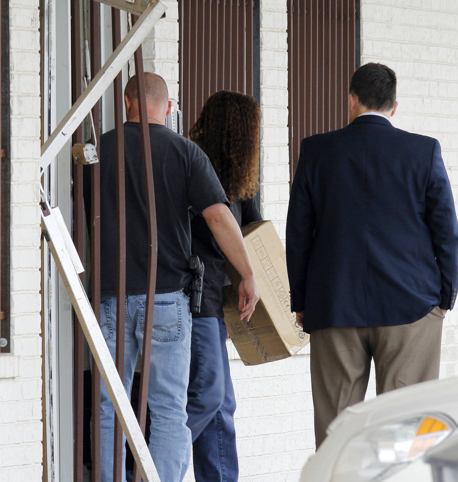 Photo - Evidence is removed Tuesday from International Internet Technologies LLC, during a search of the Anadarko business by federal and state agents.   PAUL B. SOUTHERLAND - PAUL B. SOUTHERLAND
