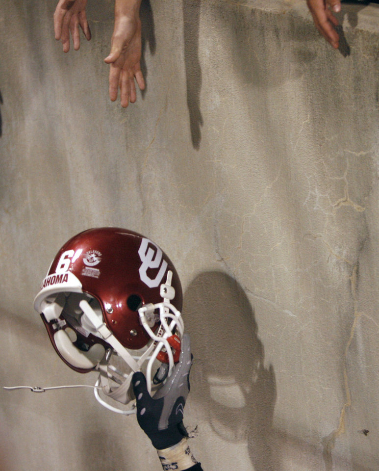 Photo - Young fans reach to touch a player's helmet after the he University of Oklahoma Sooners (OU) 41-31 victory over the University of Missouri Tigers (MU) at the Gaylord Family Oklahoma Memorial Stadium on Saturday, Oct. 13, 2007, in Norman, Okla.  By STEVE SISNEY, The Oklahoman
