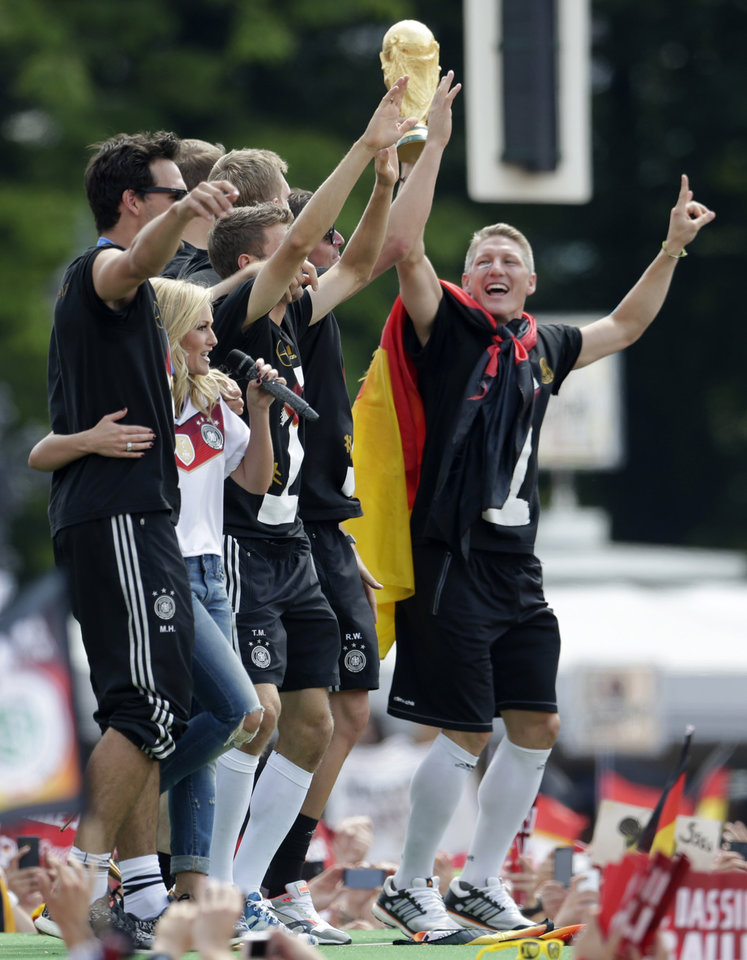 Photo - Singer Helene Fischer, second left, performs during a fan party after the arrival of the German national soccer team in Berlin Tuesday, July 15, 2014. Germany beat Argentina 1-0 on Sunday to win its fourth World Cup title.  (AP Photo/Petr David Josek)