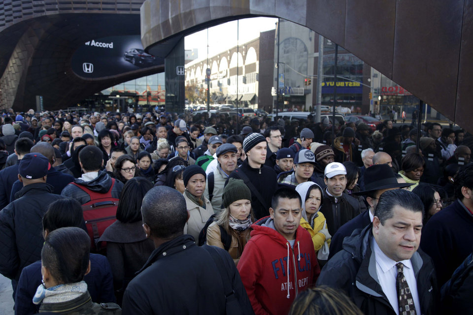 Commuters wait in a line to board busses into Manhattan in front of the Barclays Center in Brooklyn, New York, Thursday, Nov. 1, 2012.  The line streached twice around the arena and commuters reported wait times of one to three hours to get on a bus. (AP Photo/Seth Wenig) ORG XMIT: NYSW101