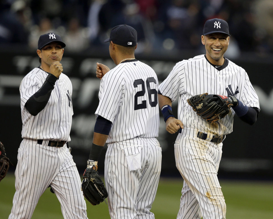 Photo - New York Yankees' Derek Jeter, right, Yangervis Solarte, center, and Brian Roberts celebrate after the Yankees' home opener baseball game against the Baltimore Orioles at Yankee Stadium, Monday, April 7, 2014, in New York. The Yankees won 4-2. (AP Photo/Seth Wenig)