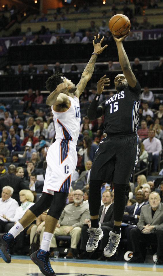 Photo - Minnesota Timberwolves forward Shabazz Muhammad, right, shoots over Charlotte Bobcats guard Chris Douglas-Roberts during the first half of an NBA basketball game in Charlotte, N.C., Friday, March 14, 2014. (AP Photo/Nell Redmond)