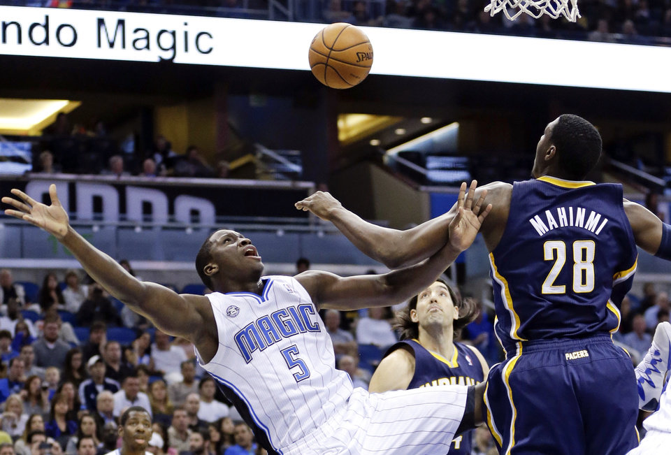Photo - Orlando Magic's Victor Oladipo (5) loses control of the ball as he goes up for a shot past Indiana Pacers' Ian Mahinmi (28), of France, during the first half of an NBA basketball game in Orlando, Fla., Sunday, Feb. 9, 2014. (AP Photo/John Raoux)