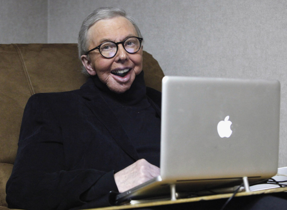 Photo - FILE - In this Jan. 12, 2011 file photo, Pulitzer Prize-winning movie critic Roger Ebert works in his office at the WTTW-TV studios in Chicago. Ebert died on Thursday, April 4, 2013. He was 70. Ebert started out as an old-school newspaper man, the kind that has all but vanished: a fierce competitor who spent the day trying to scoop the competition and the night bellied up to the bar swapping stories. Then newspapers fell on hard times, either laying off huge chunks of their staffs or disappearing altogether. But Ebert didn't merely survive. He flourished, largely by embracing television and later the Internet and social networks. (AP Photo/Charles Rex Arbogast, File)