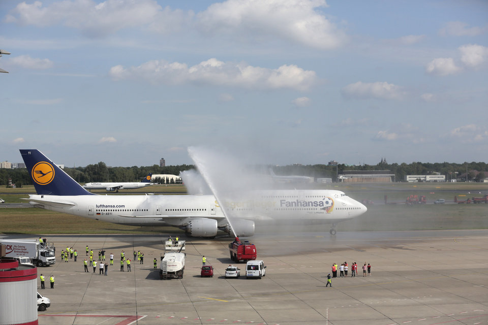 """Photo - The plane with the players of German national soccer team  arrives at Tegel airport in Berlin Tuesday, July 15, 2014.  Germany's World Cup-winning team has returned home from Brazil to celebrate the country's fourth title with huge crowds of fans. The team's Boeing 747 touched down at Berlin's Tegel airport midmorning Tuesday after flying a lap of honor over the """"fan mile"""" in front of the landmark Brandenburg Gate.  Words  on plane read: Winner Plane and instead of Lufthansa, Fanhansa.  (AP Photo/Markus Schreiber)"""