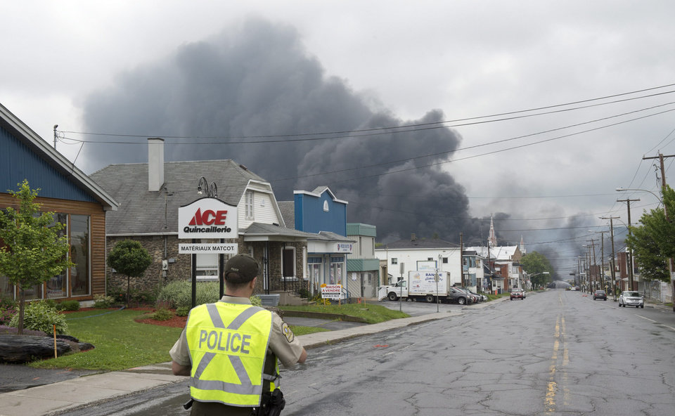 Photo - A police officer watches as smoke rises from railway cars that were carrying crude oil after derailing in downtown Lac Megantic, Que., Saturday, July 6, 2013. A large swath of Lac Megantic was destroyed Saturday after a train carrying crude oil derailed, sparking several explosions and forcing the evacuation of up to 1,000 people. (AP Photo/The Canadian Press, Paul Chiasson)