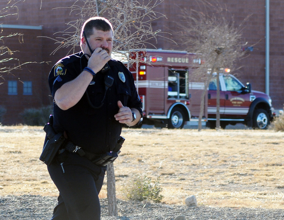 Photo - Law enforcement personnel set up a perimeter after a shooting at Berrendo Middle School, Tuesday, Jan. 14, 2014, in Roswell, N.M. A shooter opened fire at the middle school, injuring at least two students before being taken into custody. (AP Photo/Roswell Daily Record, Mark Wilson)