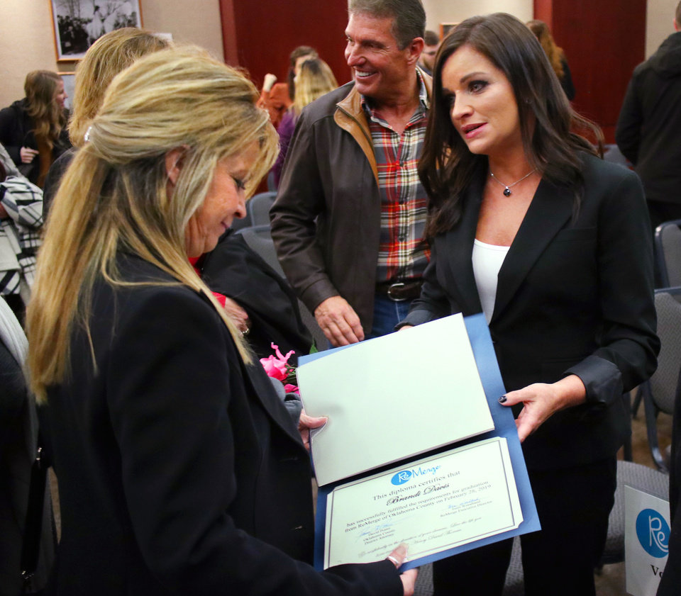 Photo - Brandi Davis mom, Cara Goettsch, looks at the diploma after the ceremony. Brandi Davis graduates from the ReMerge program in a ceremony at the Oklahoma History Center Thursday, February 28, 2019.  Photo by Doug Hoke/The Oklahoman