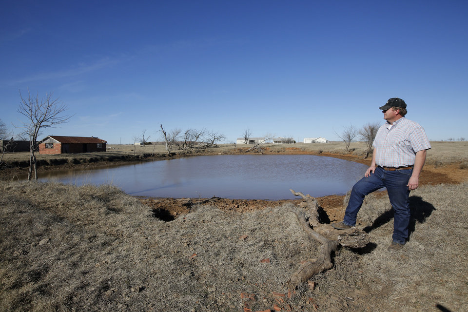 Photo -  Eric Bilderback looks at the low water level of his pond Tuesday in Canadian County. The El Reno rancher is one of many Oklahomans who have filed for drought relief. Photo By  Steve Gooch,  The Oklahoman   Steve Gooch -  The Oklahoman