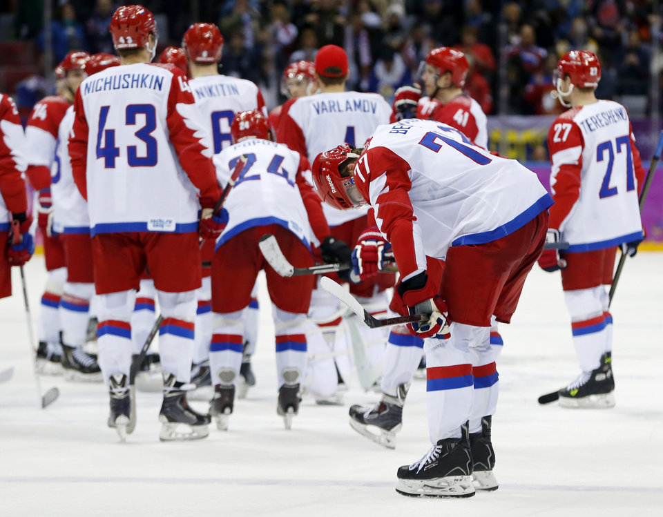 Photo - Russia defenseman Anton Belov reacts after Russia lost 3-1 to Finland in a men's quarterfinal ice hockey game at the 2014 Winter Olympics, Wednesday, Feb. 19, 2014, in Sochi, Russia. (AP Photo/Julio Cortez)