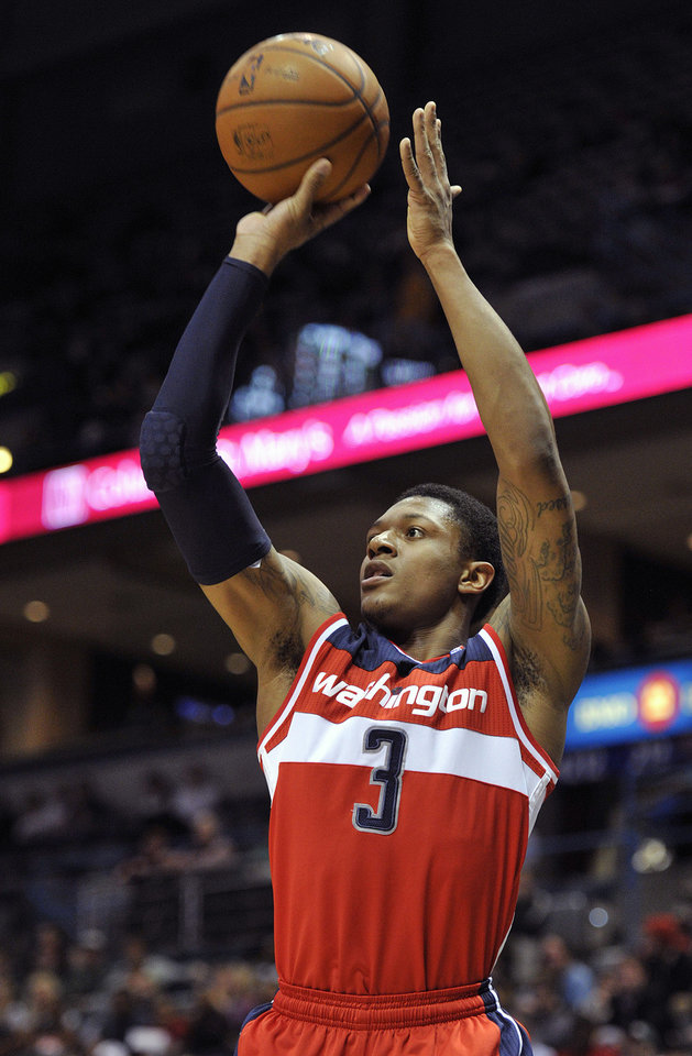 Photo - Washington Wizards' Bradley Beal (3) shoots a three point basket against the Milwaukee Bucks during the first half of an NBA basketball game Monday, Feb. 11, 2013, in Milwaukee. (AP Photo/Jim Prisching)