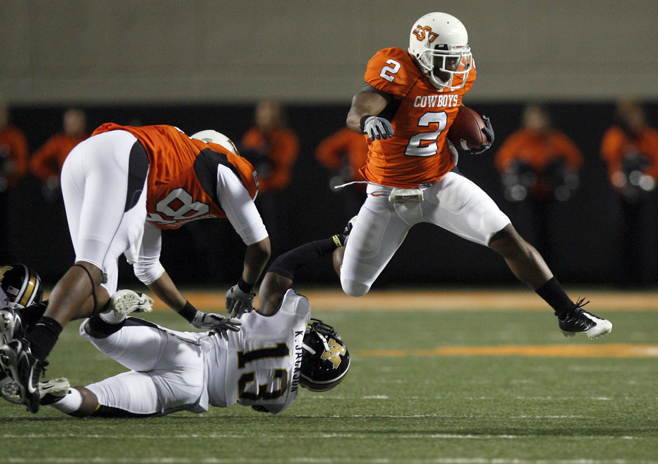Photo - OSU's Beau Johnson (2) leaps over Missouri's Kenji Jackson (13) and OSU's Wilson Youman (86) during the college football game between Oklahoma State University (OSU) and the University of Missouri (MU) at Boone Pickens Stadium in Stillwater, Okla. Saturday, Oct. 17, 2009.  Photo by Sarah Phipps, The Oklahoman